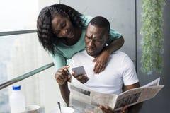 Black couple using mobile phone stock image
