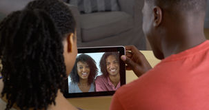 Black couple video chatting with friends on tablet. African American couple talking to friends over tablet computer video chat Stock Photo
