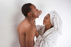Black couple wrapped in bath towel brushing teeth