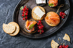 Black crackers with salmon and berries. Stack of black charcoal and traditional crackers with smoked salmon, cream cheese, green salad and red currant berries on Royalty Free Stock Photo