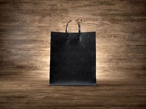 Black craft shopping bag, wood background. Focus Royalty Free Stock Images