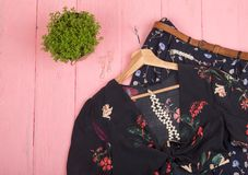 Black crop top / blouse in floral print on hangs on hanger, blue skirt, belt and jewelry: hair pearl clip, necklace, earrings on. Fashion trends - black crop top royalty free stock image