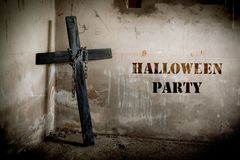 Black cross against the wall with hanging steel chain, Halloween party festival posture advertising. Halloween`s Day and ghost. Concept. Dark and scary tone stock photos