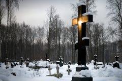 Black cross shining in the morning sunlight. Orthodox cemetery with big black cross shining in the morning sunlight Stock Photos