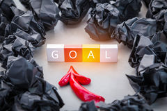 Black crumpled paper ball and red arrow with plastic block with Royalty Free Stock Image