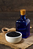 Black cumin. Nigella sativa (Black cumin) on ceramic bowl and essential oil Royalty Free Stock Image