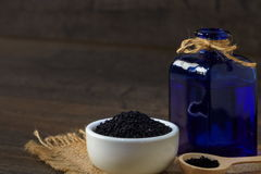 Black cumin. Nigella sativa (Black cumin) on ceramic bowl and essential oil Royalty Free Stock Images