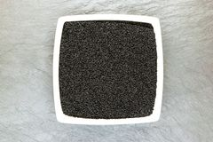 Black Cumin Nigella Sativa or Kalonji Seeds in White Plate on White Stone Background Surface with Free Space Royalty Free Stock Photo