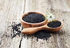 Black cumin oil with flower. On wooden board Royalty Free Stock Photos