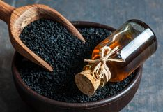 Black cumin seeds in bowl with wooden spoon essential oil. Nigella Sativa in glass bottle. Organic herbal medicine for many diseases stock photo