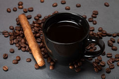 Black cup of coffee, cigar and coffee seeds on the slate background.  royalty free stock images