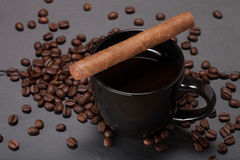 Black cup of coffee, cigar and coffee seeds on the slate background.  royalty free stock image
