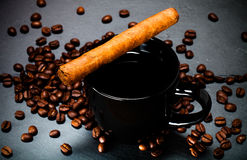 Black cup of coffee, cigar and coffee seeds on the slate background. Toned.  royalty free stock image