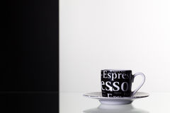 Black  cup of coffee and on a glass table Stock Images