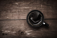 Black cup of coffee on old wooden table. Toned Royalty Free Stock Photography