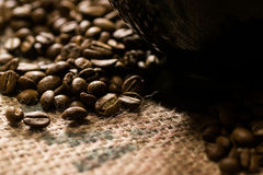 Black cup of on a coffee sack with roasted beans around. Black cup of on a coffee sack wit beans around Stock Photos
