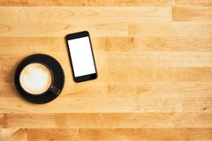 Black cup of coffee with black smartphone on wooden table. Black cup of coffee or cappuccino with black modern smartphone on yellow wooden table. Top view. Copy royalty free stock photos