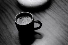 Black mug of coffee on table under lamp, monochrome Royalty Free Stock Photo