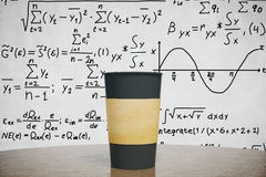 Black cup of coffee on the wooden table with equation background Royalty Free Stock Images