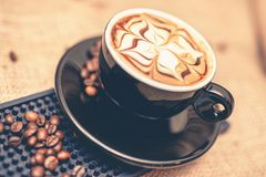 Black cup of freshly brewed espresso coffee. Close-up of coffee cup with milk and beans Royalty Free Stock Photo