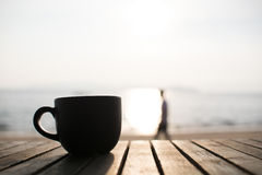 Black cup of hot coffee on the wood table and blur person in bac Royalty Free Stock Photos