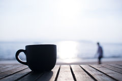 Black cup of hot coffee on the wood table and blur person in bac Royalty Free Stock Image