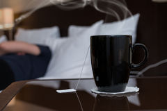 Black cup of hot tea. On a glass table in a hotel room stock photo
