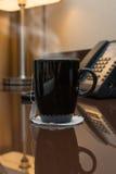 Black cup of hot tea Stock Photos