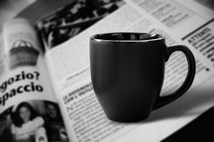 Black cup and newspaper. Photo of black empty cup of coffee on newspaper royalty free stock photos
