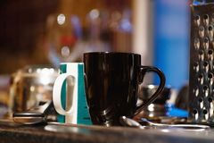 Black cup and other dishes on a kitchen table. Close up stock photo