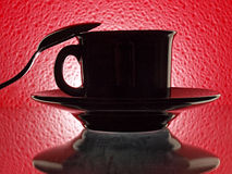 Black Cup, Saucer snd Spoon. Photo of a coffee cup, saucer and spoon on red background Royalty Free Stock Photography