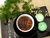 Black cup of tea with green branch and candles over straw matt stock images