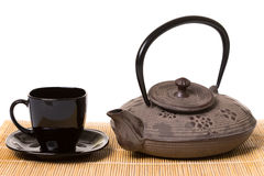 Black cup of tea on saucer and iron teapot on wooden mat. Stock Photos
