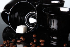 Black cups and beans of coffee Stock Images