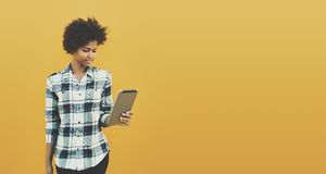 Black curly girl with digital tablet on yellow background Stock Images