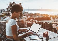 Black curly lady with laptop, digital pad and vintage camera royalty free stock photography