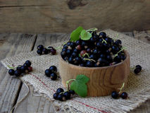 Black currant in a basket. On a wooden background royalty free stock photography