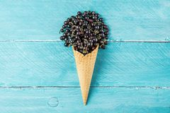 Black currant berries in waffle ice cream cone on blue wooden background. creative summer food concept. flat lay. Top view stock images