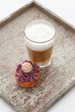 Black currant buttercream cupcake with glass of latte Royalty Free Stock Image