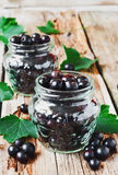 Black currant. Fresh black currant in a glass jar on the old wooden background. natural vitamins and nutrients.health and diet food Stock Image