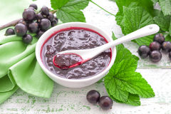 Black currant jam. In a bowl and fresh berries with leaves royalty free stock photography