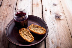 Black currant jam in glass jar and crackers Stock Photography