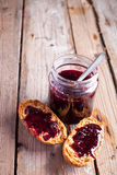 Black currant jam in glass jar and crackers Stock Image