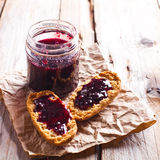 Black currant jam in glass jar and crackers Stock Photo