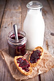 Black currant jam in glass jar, milk and crackers Stock Photo