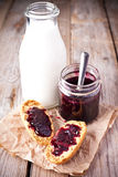 Black currant jam in glass jar, milk and crackers Royalty Free Stock Photos