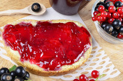 Black currant jam on a slice and in a jar Royalty Free Stock Photos