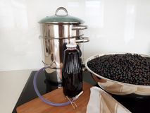 Black currant juice making by steam juicer pot in the kitchen stock photography