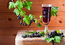 Black currant liquor and ripe berries. On wooden table royalty free stock image