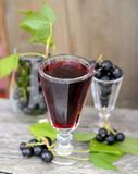 Black currant liquor and ripe berries on wooden. Table. Selective focus stock photography